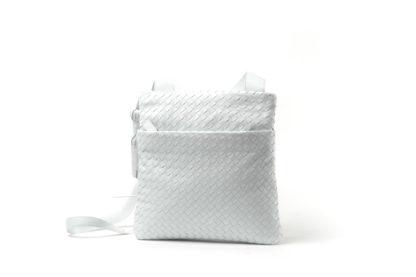 Handtasche in weiß, geflochten und einem langem Riemen zum Quertragen.