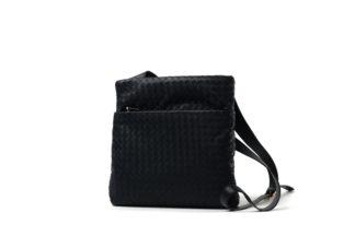 Handtasche schwarz mit geflochtenem Leder und einem langem Riemen zum Quertragen.